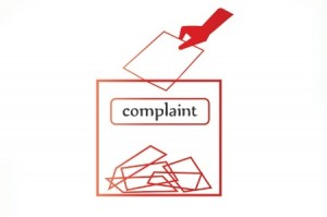 hand_putting_note_into_complaints_bo_450
